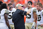 Wake Forest Demon Deacons head coach Dave Clawson goes over the coin toss strategy with his team captains prior to the game against the Clemson Tigers at Memorial Stadium on October 7, 2017 in Clemson, South Carolina.  The Tigers defeated the Demon Deacons 28-14. (Brian Westerholt/Sports On Film)