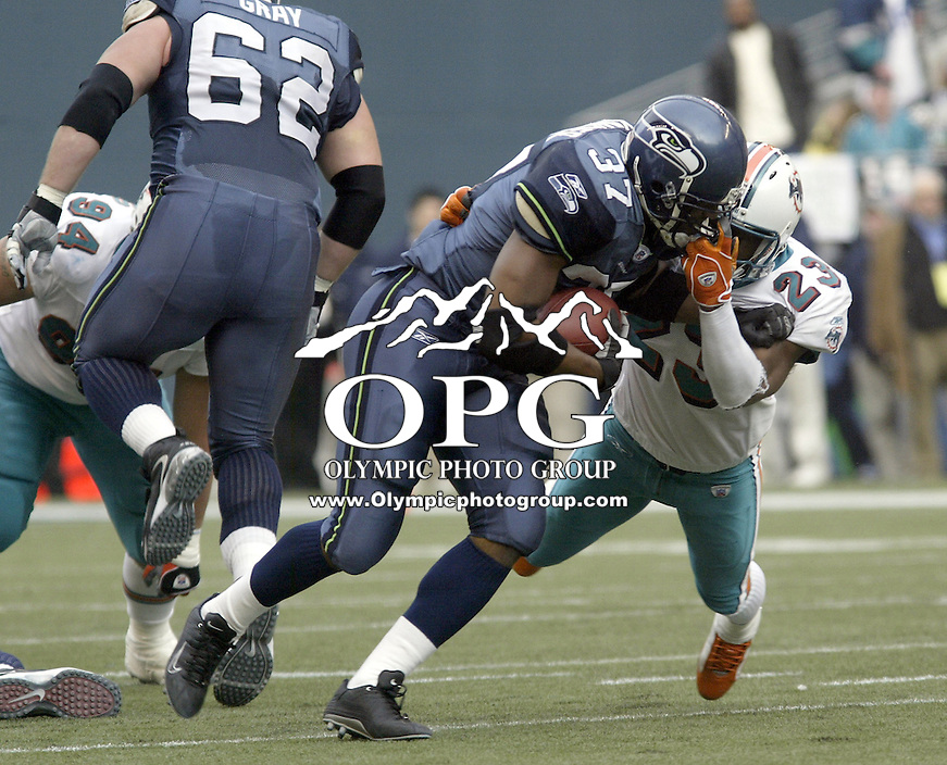 Seattle Seahawks running back Shaun Alexander tries to fight off a face mask from Miami Dolphins corner back Patrick Surtain at Quest field in Seattle, WA.