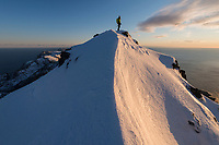 Female hiker on narrow summit ridge in winter of Mannen mountain peak, Moskenesøy, Lofoten Islands, Norway