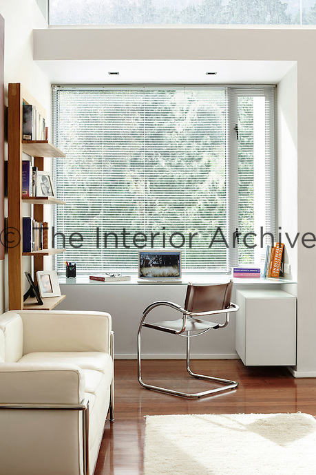A stylish, contemporary study area with plenty of light for working. The white walls, polished wood floor and classic furniture, such as the white leather Le Corbusier sofa, give the space a clean, minimal feel.