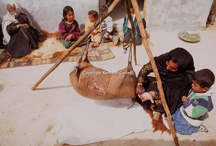 Bedouin woman making butter or cheese in goat skin bag, Jordan