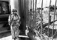 U.S. Marine Lance Cpl. Shawn Thacker stands guard at the gate of the U.S. embassy in Mogadishu, Somalia in February 1993 while two Somalia boys look through.