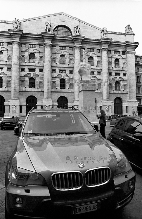 milano. L.O.V.E., la scultura dell'artista maurizio cattelan raffigurante una mano con le dita mozzate tranne il dito medio, esposta in piazza affari davanti alla borsa. un suv bmw parcheggiato davanti l'opera --- milan. L.O.V.E., the sculpture of a hand with all fingers cut off except the middle finger, of the artist maurizio cattelan, exposed in affari square in front of the stock exchange. a suv bmw parked in front of the artwork