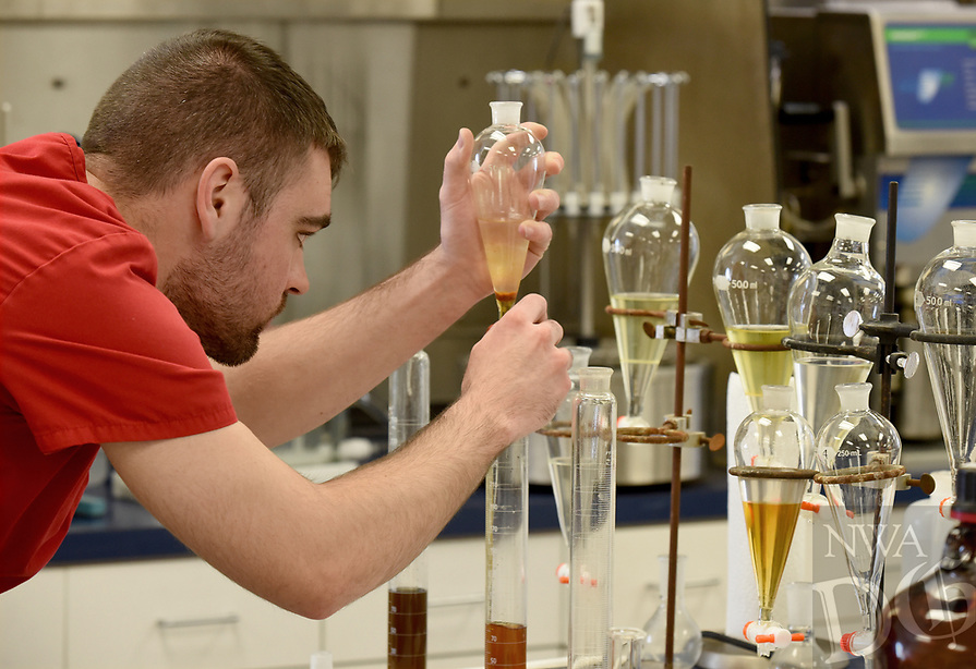 NWA Democrat-Gazette/DAVID GOTTSCHALK Travis Altemeier, director of chemistry, measures solutions Friday, March 22, 2019, in the Chemistry Department at Whitbeck Laboratories in Springdale. The business is located on a corner lot of the industrial park in the city.