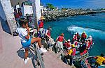 Enfant des Galapagos en train de regarder les touristes qui embarquent pour une croisiere
