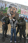 An Israeli soldiers detain a Palestinian demonstrator in front of a mural depicting the late Palestinian leader Yasser Arafat on the controversial Israeli barrier during the clashes at Qalandia checkpoint lead from the West Bank to Jerusalem on 19 March 2010. Clashes continue on 19 March in the West Bank amid growing anger over the announcement of further Israeli settlement expansion. Israeli fighter jets have also struck at least half a dozen targets in Gaza. Photo by Issam Rimawi
