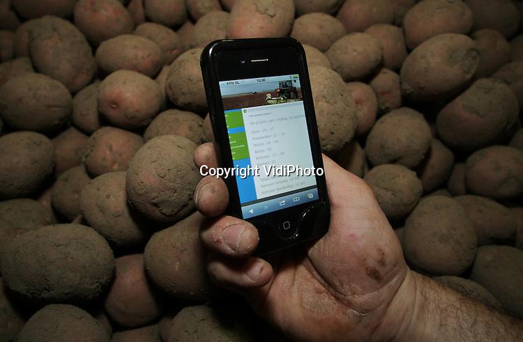 Foto: VidiPhoto..RANDWIJK - Een akkerbouwer bekijkt de meest recente aardappelprijzen op zijn smartfoon. Steeds meer boeren maken gebruikt van smartfoons om op de hoogte te blijven van het laatste landbouwnieuws of maken gebruik van sociale media..
