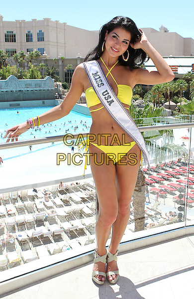 RIMA FAKIH  - MISS USA 2010.Media Day At Mandalay Bay Beach At Mandalay Bay Resort Casino, Las Vegas, Nevada, USA, 24th June 2010..full length yellow bikini sash beauty queen hand touching hair .CAP/ADM/MJT.© MJT/AdMedia/Capital Pictures.