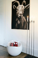 A group of tall metal candlesticks in front of a black and white photograph of a goat in the entrance hall