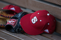 A North Carolina State Wolfpack cap sits on top of a glove on the bench during the game against the Charlotte 49ers at BB&T Ballpark on March 31, 2015 in Charlotte, North Carolina.  The Wolfpack defeated the 49ers 10-6.  (Brian Westerholt/Four Seam Images)