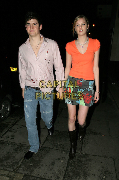 JAMES ALEXANDROU & GIRLFRIEND.Brits after party at Kensington Roof Gardens.17 February 2004.full length, full-length, denim jeans, bright red t-shirt, orange, print miniskirt, knee length boots.www.capitalpictures.com.sales@capitalpictures.com.© Capital Pictures.