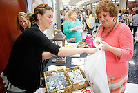 NWA Democrat-Gazette/DAVID GOTTSCHALK  Kathy Passmore (right), with George Elementary School, receives items from Morgan Hill, with Join the Solution, during the Springdale School District annual appreciation breakfast at Springdale High School Monday, August 10, 2015. The teachers received items from vendors, ate breakfast and participated in a welcoming program.
