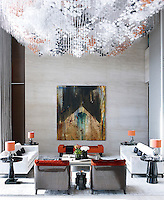 A spectacular custom lighting sculpture acts as a canopy above one social seating group shaped with Christian Liaigre's velvet sofas and spicy red chairs. A low-lying red velvet bench primly shows its lustre beneath Walking On My Left Foot from the owner's private art collection.