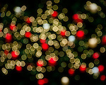 A blur of bokeh lights in red and white in the city at Christmastime.