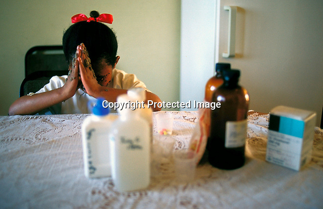disiaids00444  Social Issues, Aids: Jady Graslund, age 9, is praying before taking her antiretroviral HIV-Aids drugs around 7 in the morning on November 28, 2002. Jady is living with HIV and takes drugs two times a day. She goes to a normal school and is fully accepted by the pupils and the teachers. Her mother died of an Aids related disease in 1996 and she is taken care of by an aunt. Judy visits about three hospitals a week for treatment. She is one of the fortunate South African's that receives Aids drugs. The country is struggling with one of the highest HIV-Aids infection rates in the world. .©Per-Anders Pettersson/iAfrika Photos..