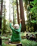 USA, California, Eureka, senior woman sitting redwood forest looking at trees