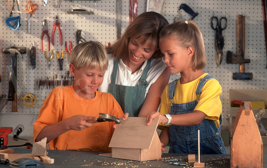 Mother works on birdhouse project with children.