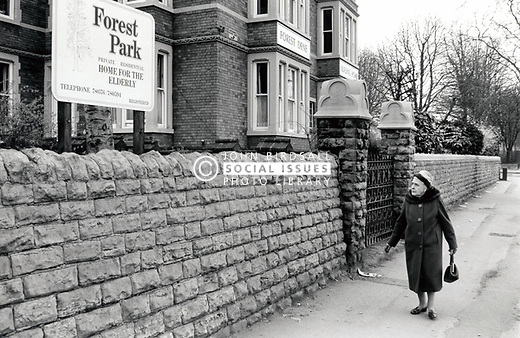 Elderly woman walking past private residential home for the elderly, Nottingham UK 1985