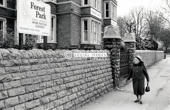 Elderly woman walking past private residential home for the elderly, Nottingham UK 1985