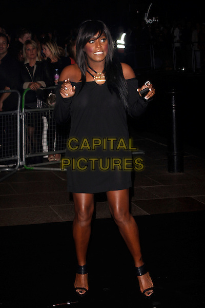 MICA PARIS.The Ozwald Boateng Fashion Show during the final day of London Fashion Week, Odeon cinema Leicester Square London, England, UK..September 22nd 2010.full length black dress off the shoulders hands funny long sleeve ankle strap sandals platform .CAP/AH.©Adam Houghton/Capital Pictures.