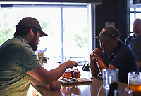 NWA Democrat-Gazette/CHARLIE KAIJO Bartender John Jolly (left) serves a flight of beer to Sonephet Manivong of Grand Island, Neb. (right), Thursday, August 8, 2019 at the Bike Rack Brewing in Bentonville.<br /> <br /> Bike Rack Brewing is distributing into Little Rock now.