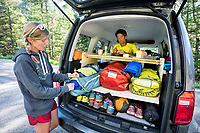 A woman packs a duffel bag in the back of a car while inside a man sits working