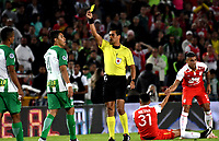 BOGOTÁ - COLOMBIA, 17-01-2019: Ferney Trujillo (Cent.), árbitro, muestra tarjeta amarilla a Brayan Rovira (Izq.), jugador de Atlético Nacional, durante partido entre Independiente Santa Fe y Atlético Nacional, por el Torneo Fox Sports 2019, jugado en el estadio Nemesio Camacho El Campin de la ciudad de Bogota. / Ferney Trujillo (C), referee, shows yellow card to Brayan Rovira (L) player of Atletico Nacional, during a match between Independiente Santa Fe and Atletico Nacional, for the Fox Sports Tournament 2019, played at the Nemesio Camacho El Campin stadium in the city of Bogota. Photo: VizzorImage / Luis Ramírez / Staff.