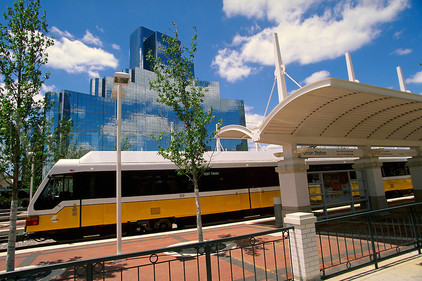 A state of the art electrically powered light rail vehicle passes through the station canopy at Union Station. Dallas Texas USA.