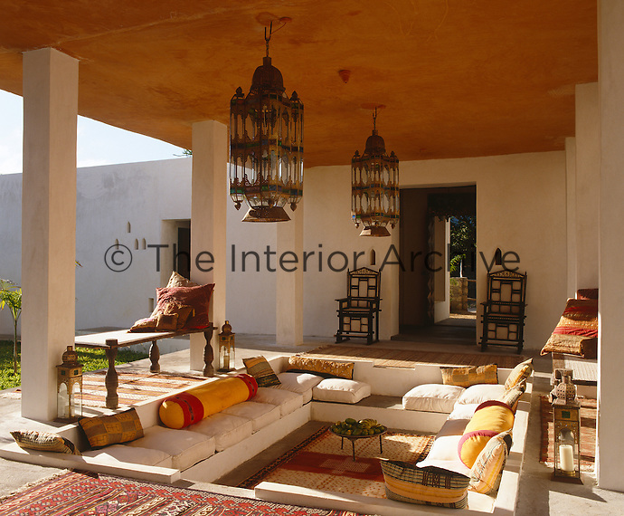 A sunken seating area above which hangs a pair of  large Moroccan lanterns forms the focal point of this sun-drenched porch