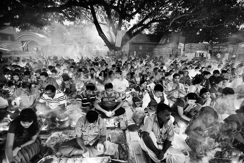 """During Kartik, """"the holiest month"""" beginning every year with the new moon in November, thousands of Hindu devotees celebrate the feast of Rakher Upobash, fasting and praying the gods sitting before the Shri Shri Lokanath Brahmachari Ashram, among the Swami Bagh Temple near Dhaka, Bangladesh. The worshippers offer candles called Prodip, meditate, give to charity, and generally perform austerity. <br /> Faithful absorbed in prayer.<br />  Barodi, Dhaka, Bangladesh. Nov. 15, 2014"""