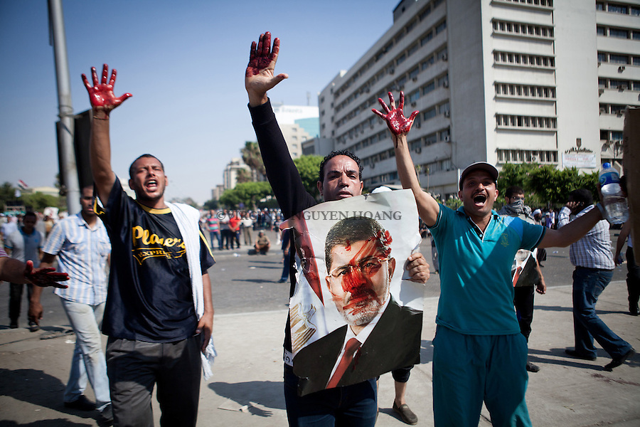 Des manifestants montrent leurs main pleine de sang de leur compatriote bless&eacute; apr&egrave;s que les troupes &eacute;gyptiennes ont ouvert le feu sur des manifestants marchant vers le si&egrave;ge de la Garde R&eacute;publicaine pour exiger le retour du pr&eacute;sident d&eacute;chu Mohammed Morsi. Les violences ont &eacute;clat&eacute; lorsque des dizaines de milliers des partisans de Morsi  sont arriv&eacute; au si&egrave;ge en scandant &quot;A bas le r&eacute;gime. <br /> <br /> Demonstrators show their hands full of blood after Egyptian troops opened fire on protesters marching toward the headquarters of the Republican Guard to demand the return of ousted President Mohammed Morsi. The violence erupted when tens of thousands of supporters of Morsi arrived at headquarters chanting &quot;Down with the regime&quot;.