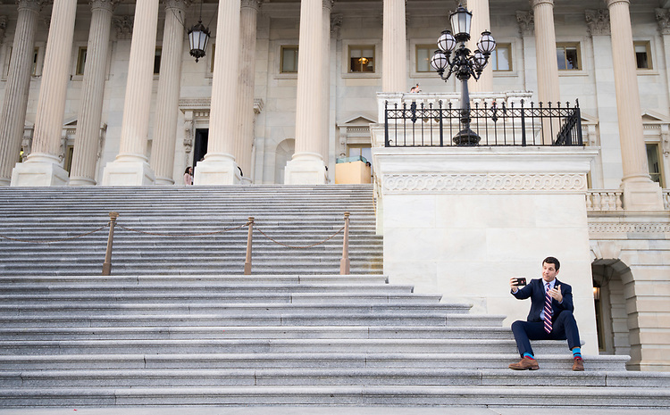 UNITED STATES - NOVEMBER 16: Rep. Scott Taylor, R-Va., sits on the House steps to do a selfie video about his vote on tax reform on Thursday, Nov. 16, 2017. (Photo By Bill Clark/CQ Roll Call)