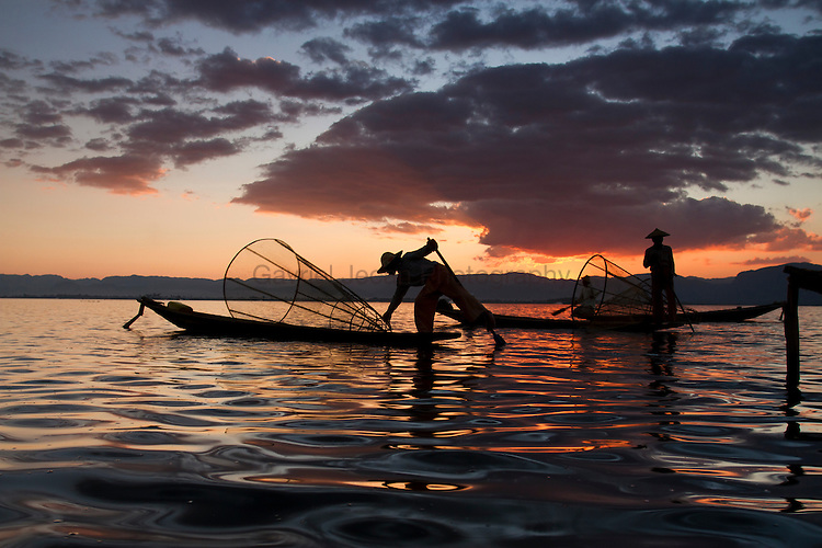 Intha fishermn with a traditional fish trap and wooden boat on Inle lake.