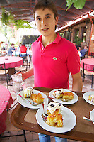 Waiter serving typical Greek dishes. Rakokazano restaurant in Strantza village near Naoussa. Macedonia, Greece.