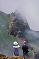 Two women in casual clothing observing the cloudy landscape of HALEAKALA NATIONAL PARK on Maui in Hawaii USA