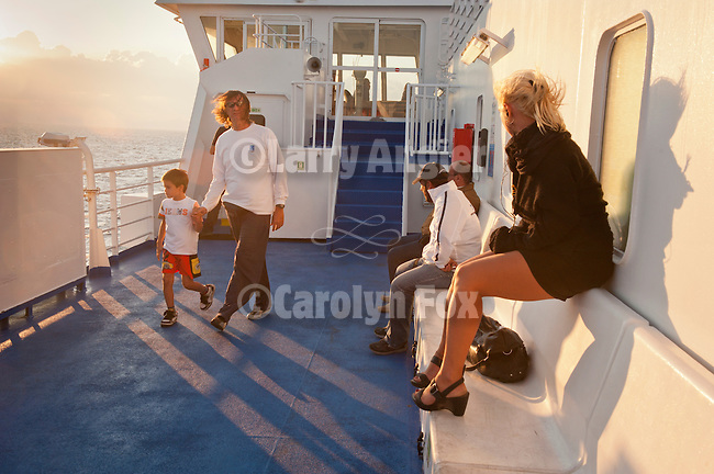 Passengers walk on the deck of the Blue Star Ferry Boat Ithaki at sundown on the Saronikos Kolpos gulf in the Aegean Sea approaching the port of Piraeus, Athens, Greece