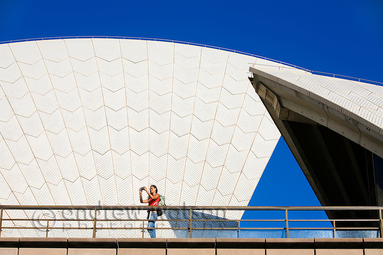 A tourist stands beneath the sail-like roofs of the Sydney Opera House.  Sydney, New South Wales, AUSTRALIA.