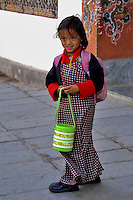 A young elementary student dressed in traditional red and black dress is headed to school with her pink backpack and lime-green lunch bucket in Thimpu, Bhutan's Capital city.