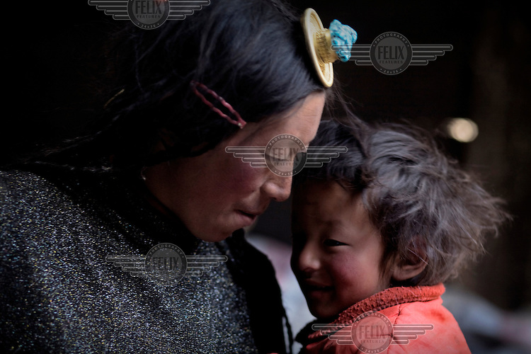 A nomadic Khampa woman and child in their home in the far west of the province.