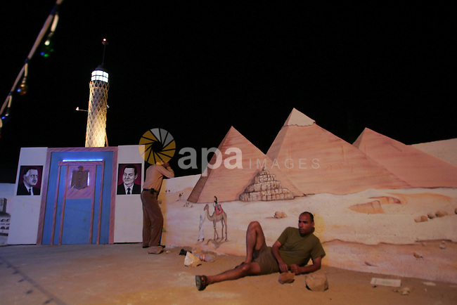 A Palestinian man sit on one side of the roof of his house in the southern Gaza Strip town of Rafah, near the border with Egypt, on July 14, 2010, where he has recreated Egypt's landmark sites with mural paintings and sculptures, including the Pyramids of Giza and a remake of an Um Kulthum Cafe, named after the late Egyptian diva who died in 1975. Photo by Hatem Omar