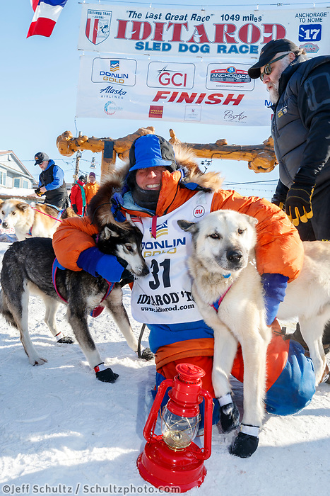 Last place finisher and Red Lantern Award winner Cindy Abbott poses with her lead dog in Nome during the 2017 Iditarod on Saturday March 18, 2017.<br /> <br /> Photo by Jeff Schultz/SchultzPhoto.com  (C) 2017  ALL RIGHTS RESERVED