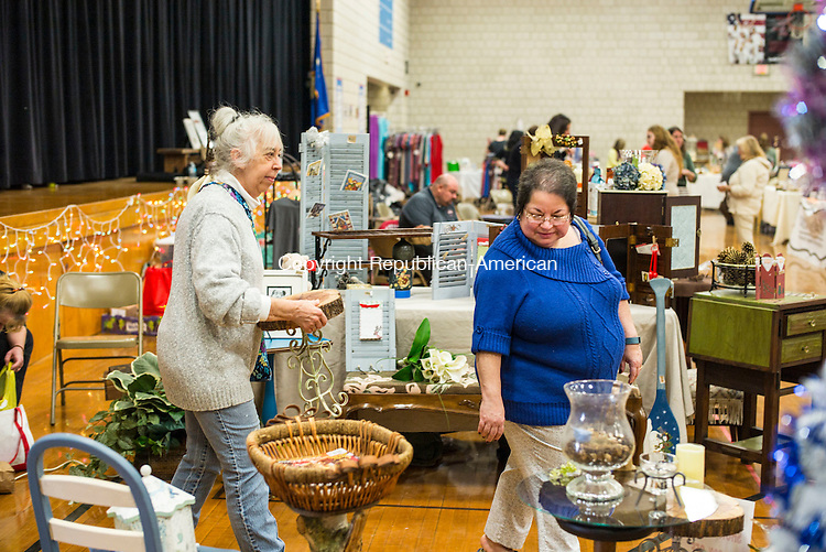 Woodbury, CT- 19 November 2016-111916CM06- Madeleine Ruggiero, left buys a wooden stool with Donna Gorton, both of Woodbury, during a bazaar at Woodbury Middle School on Saturday.  The event was put on by the Nonnewaug High School Grad Nite committee and featured 50 vendors selling various crafts and goods. Proceeds from the fair will  benefit Graduation Night festivities.  Christopher Massa Republican-American
