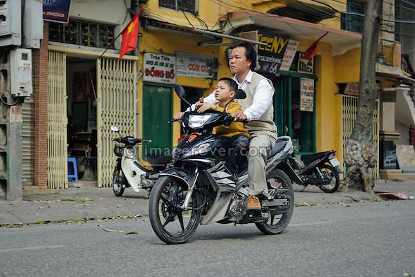 Asia, Vietnam, Hanoi. Hanoi old quarter. Father and son riding on small motorbike through Hanoi.