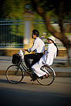 Asia, Vietnam, Hue. Boy and girls in traditional vietnamese white dress riding on one bicycle.