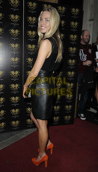 Noelle Reno<br /> The Lipsy VIP Fashion Awards 2013, DSTRKT, Rupert St., London, England.<br /> May 29th, 2013<br /> full length black leather skirt top side looking over shoulder bag orange shoes <br /> CAP/CAN<br /> &copy;Can Nguyen/Capital Pictures