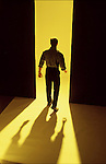Man on yellow seamless walking away from camera