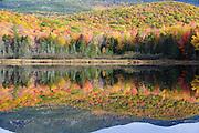Reflection of autumn foliage in Kiah Pond in Sandwich, New Hampshire USA during the autumn season.