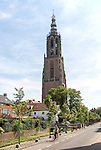Woman cycling by Gothic church clock tower, Onze Lieve Vrouwetoren, Amersfoort, Netherlands
