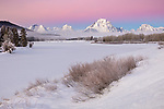 Grand Teton National Park, WY:  Mount Moran and Teton Range at dawn with low lying fog from the Oxbow of the Snake River in winter
