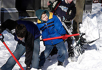 From left, Joey Mannino, Alessio Mannino, and Giovanni Mannino shovel snow from their father's storefront after a winter snow storm closed schools December 9, 2005 in Doylestown, Pennsylvania. The Philadelphia region was hit with alomst 8 inches of snow, closing schools and some businesses. Photo by William Thomas Cain / photodx.com
